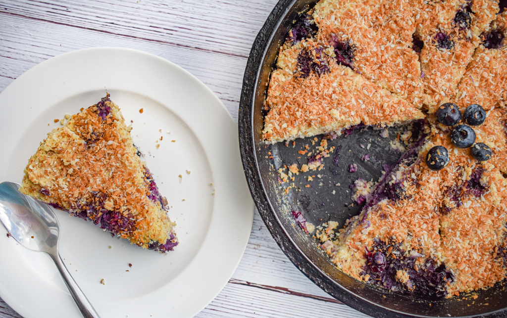 keto blueberry toasted coconut skillet cake in cast iron skillet with one slice missing and slice on white plate on the left