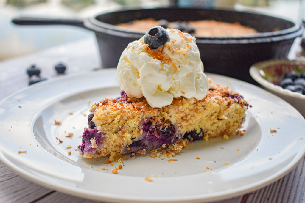 keto blueberry toasted coconut skillet cake slice topped with ice cream with cast iron and blueberries in the background
