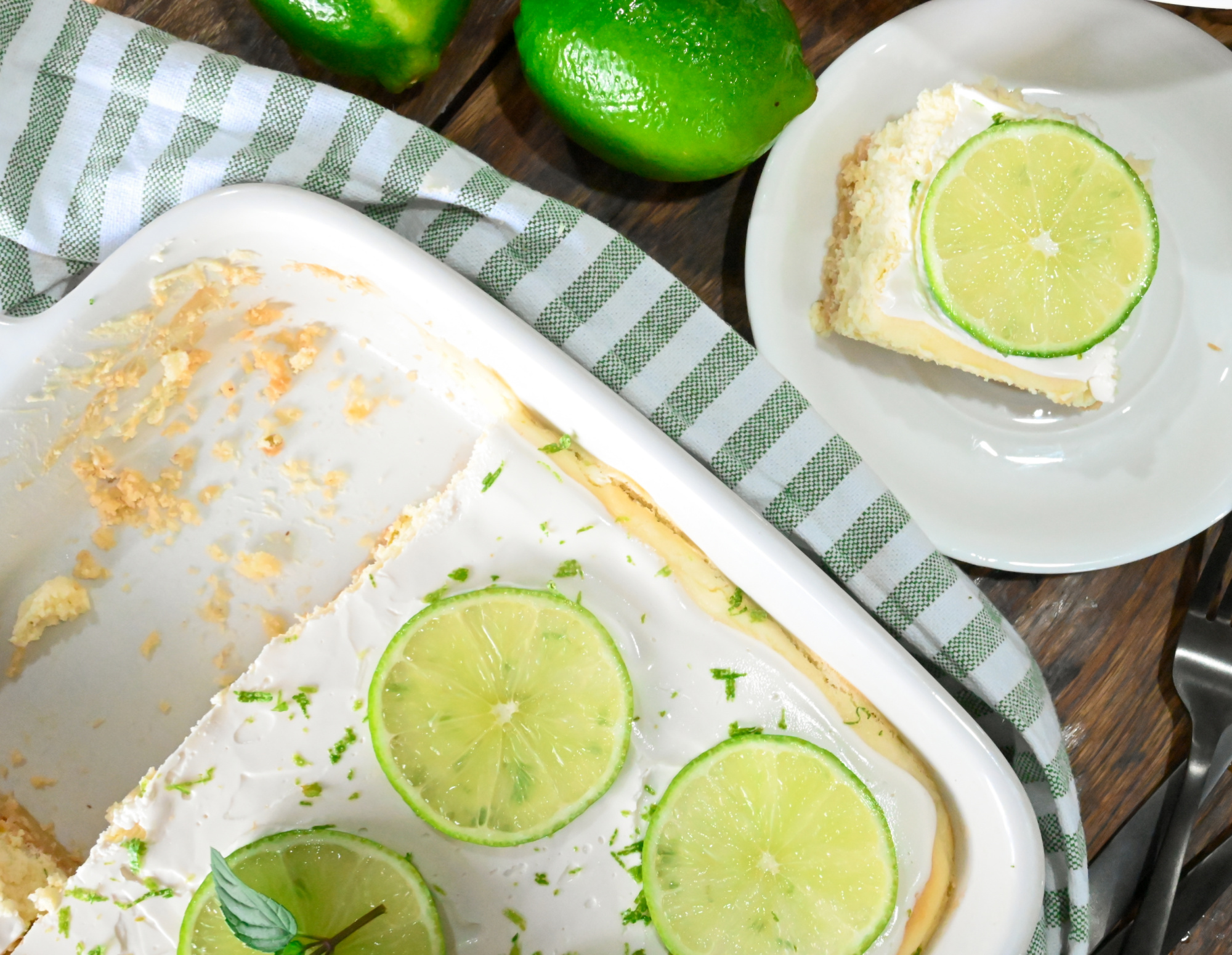 keto lime cheesecake bars sliced and served on wooden board the cheesecake has slices of lime on the top