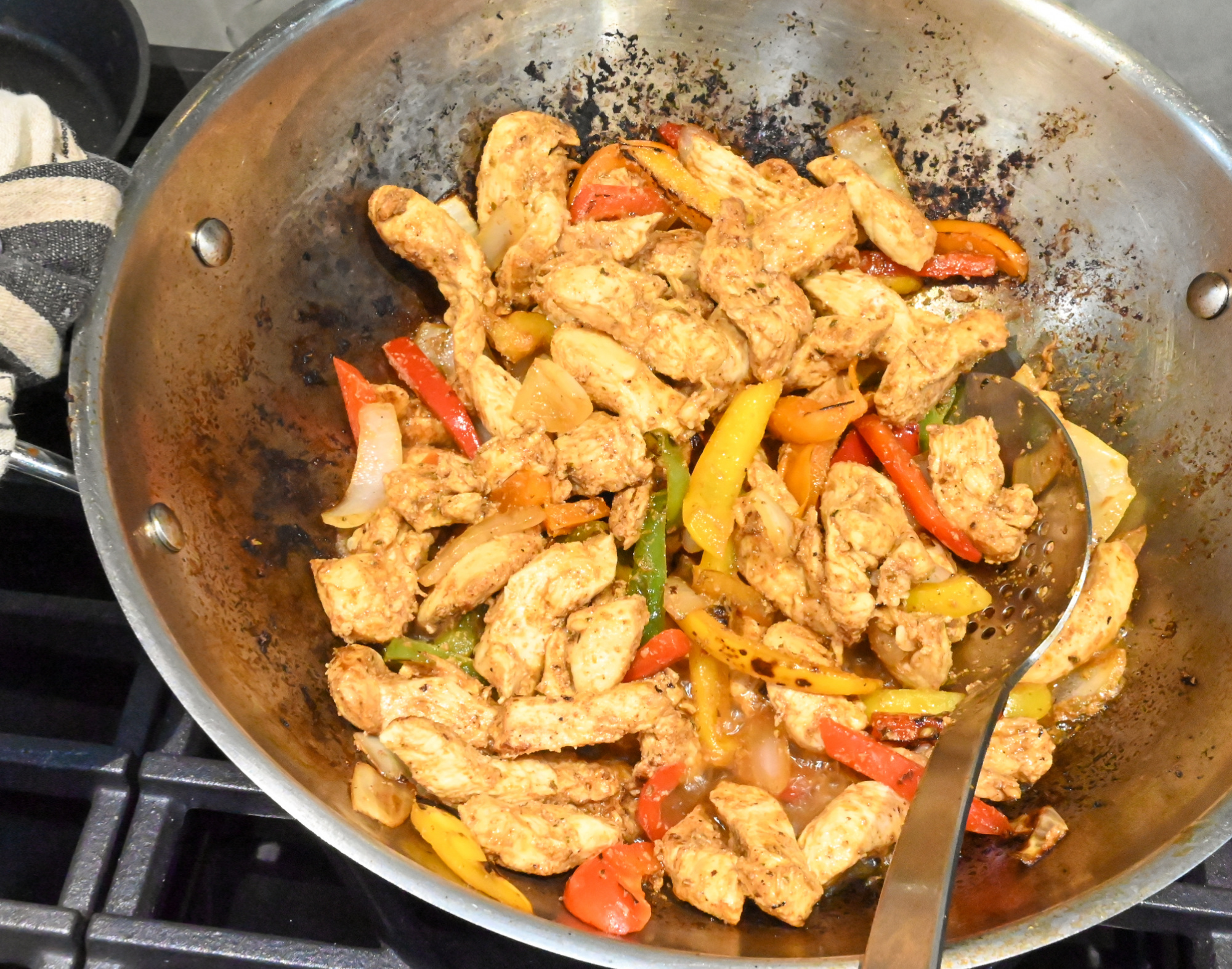 chicken fajitas being cooked in a large wok