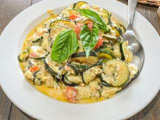 keto baked feta zucchini served in large white dish topped with fresh basil up close