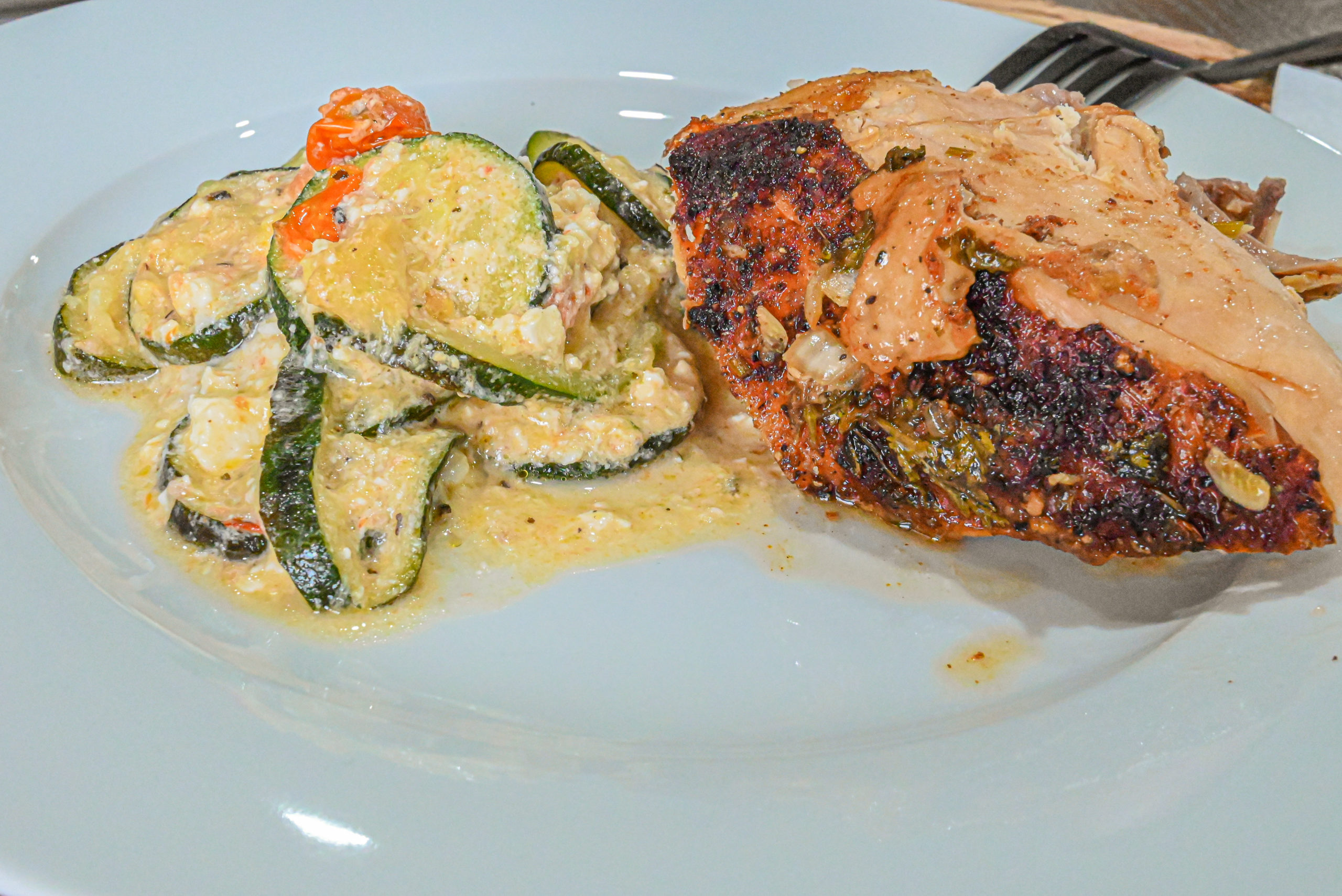 keto baked feta zucchini served with roasted chicken on white plate