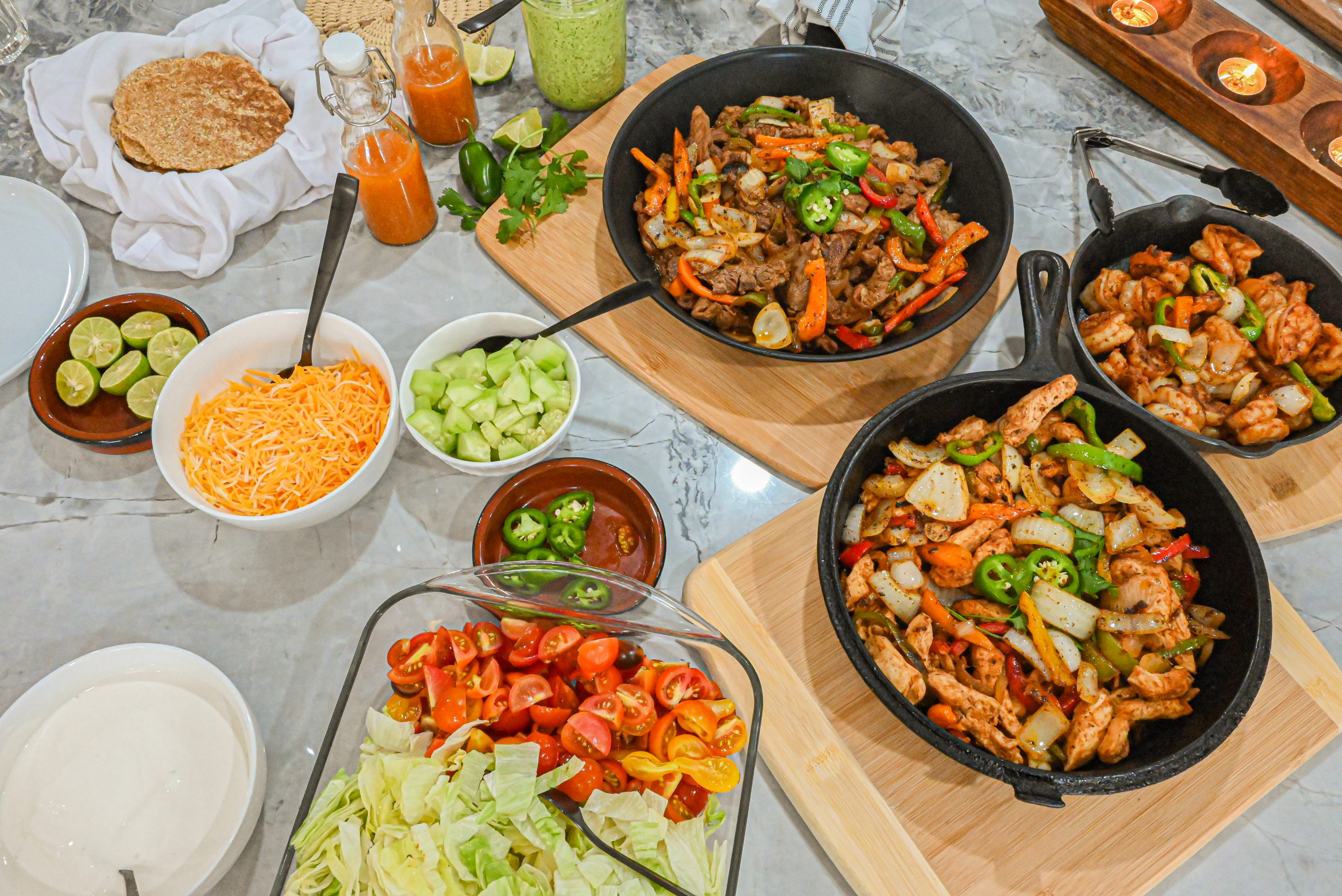 keto fajitas in skillets on counter with various sides surrounding