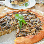 keto mushroom galette with slice removed and white plate with slice and fork in background