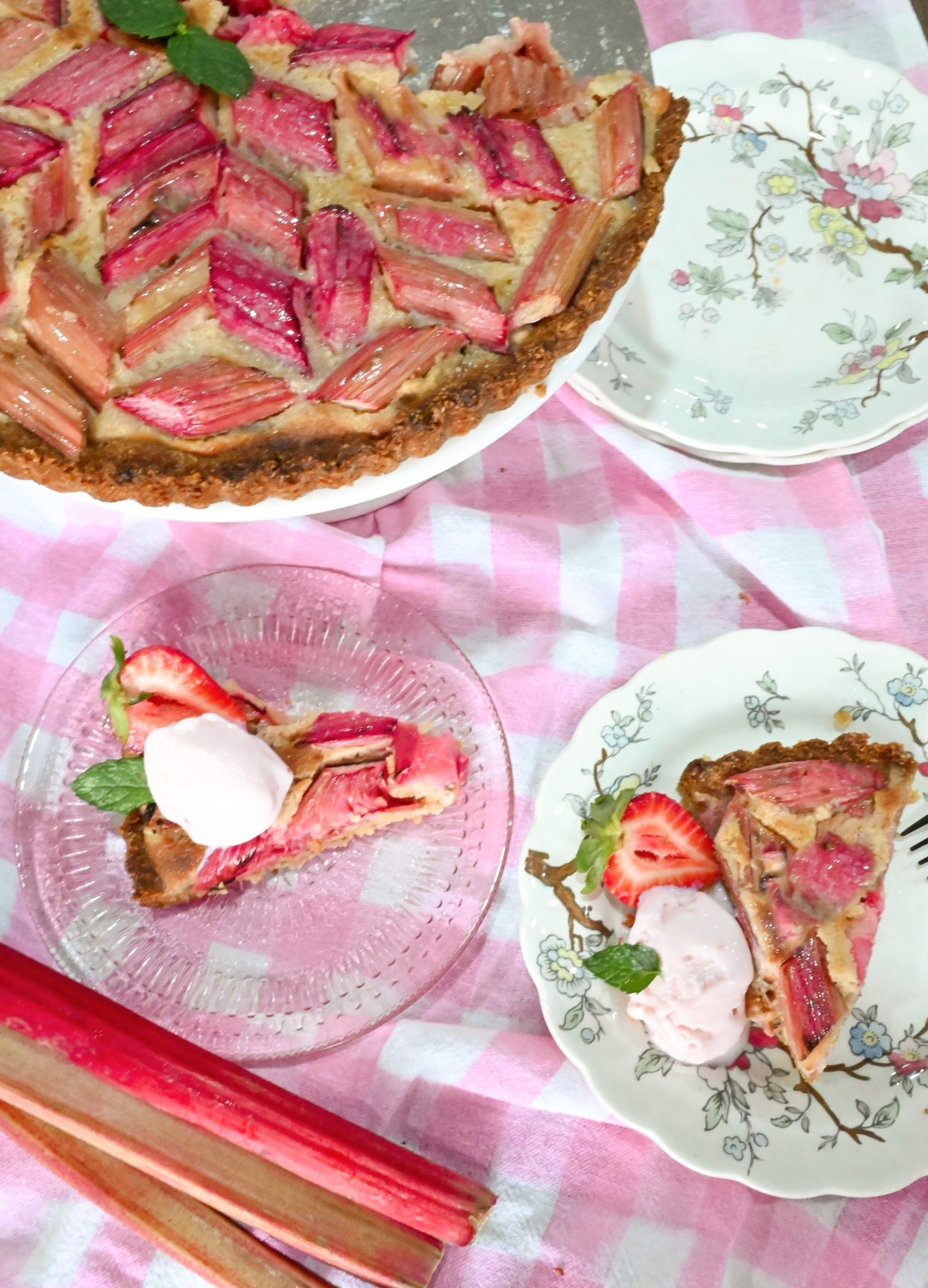 keto rhubarb tart on cake stand and sliced on a clear pink dish and floral white dish