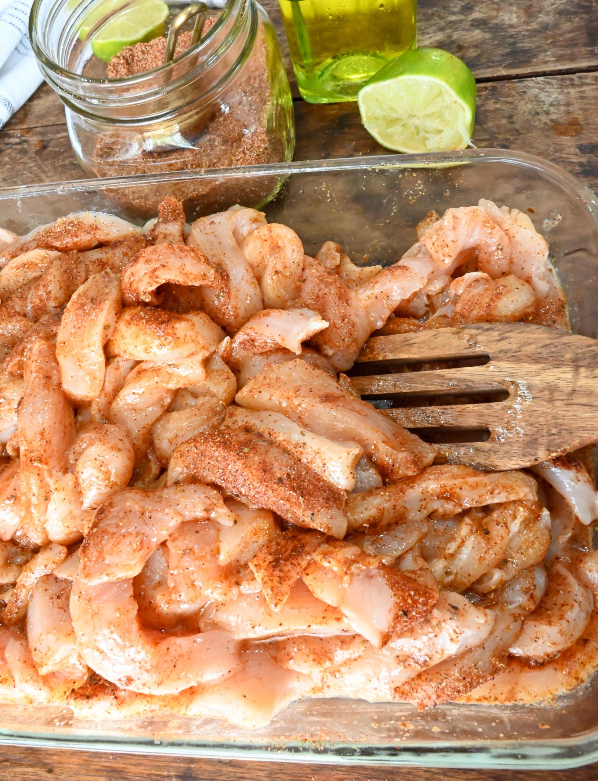 raw chicken being seasoned by keto fajita seasoning