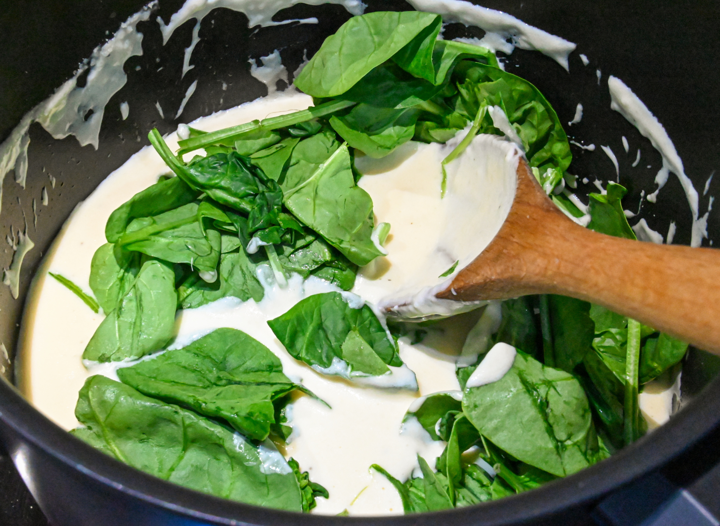 fresh spinach being added to the base of low carb spinach soup