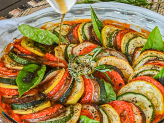 keto ratatouille in clear baking dish with vinaigrette being drizzled on top