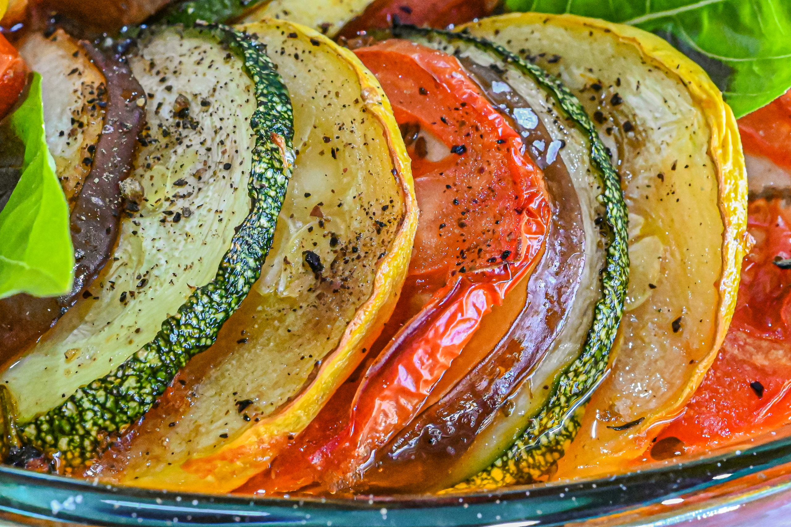 keto ratatouille slices of vegetables close up in clear baking dish